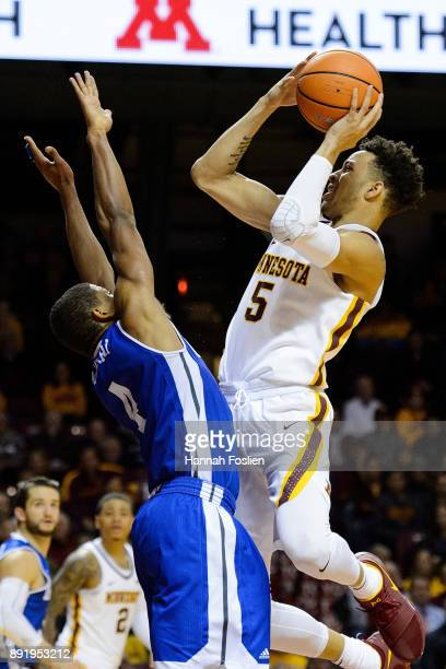 De'Antae McMurray of the Drake Bulldogs defends against Amir Coffey of the Minnesota Golden Gophers during the game on December 11 2017 at Williams...