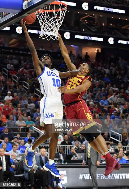 De'Anthony Melton of the USC Trojans fouls Isaac Hamilton of the UCLA Bruins as he scores on a layup during a quarterfinal game of the Pac12...