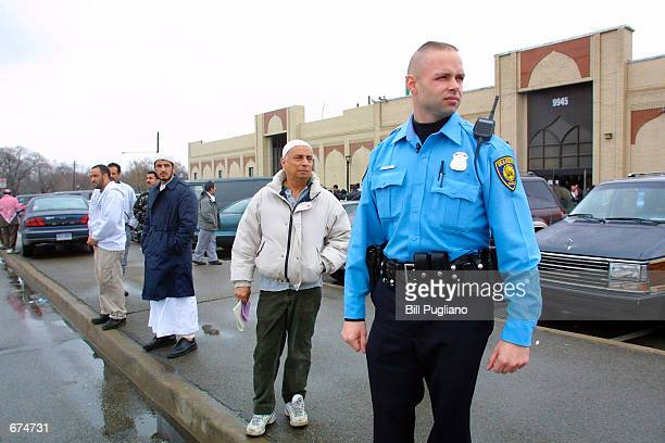 Dearborn police officer stands guard while a group of Muslims leave their mosque November 30 2001 in Dearborn MI More than 600 men in Michigan which...