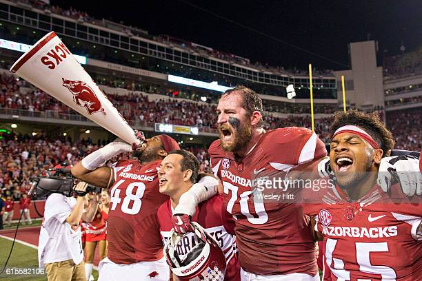 Deatrich Wise Jr #48 Dan Skipper and Josh Harris of the Arkansas Razorbacks sing with the fans after a game against the Mississippi Rebels at...