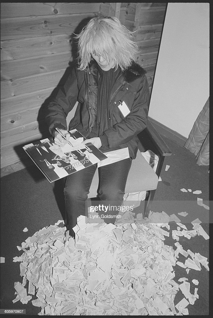 Debbie Harry of Blondie write on a piece of paper on top of her record album Parallel Lines Beneath her is a pile of papers