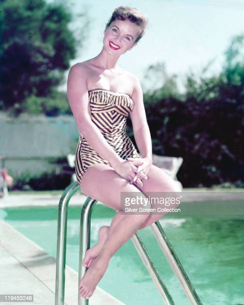 Debbie Reynolds US actress singer and dancer smiling while wearing a swimsuit sitting beside a swimming pool circa 1955