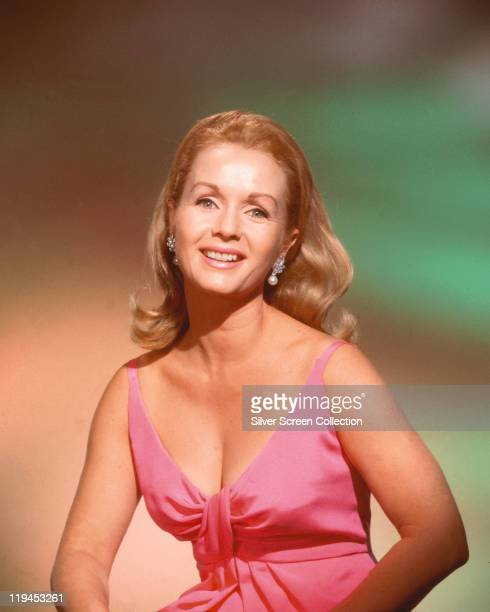 Debbie Reynolds US actress singer and dancer wearing a pink sleeveless top in a studio portrait circa 1965