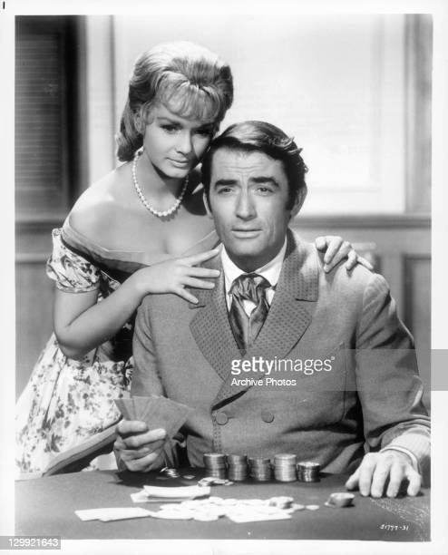 Debbie Reynolds with her hands on Gregory Peck in a scene from the film 'How The West Was Won' 1962
