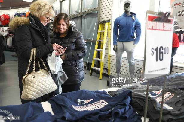 Debbie Ryan left of Medford calls her son to check his size She shops with her niece Christie Pace of Wakefield New England Patriots fans shop for...
