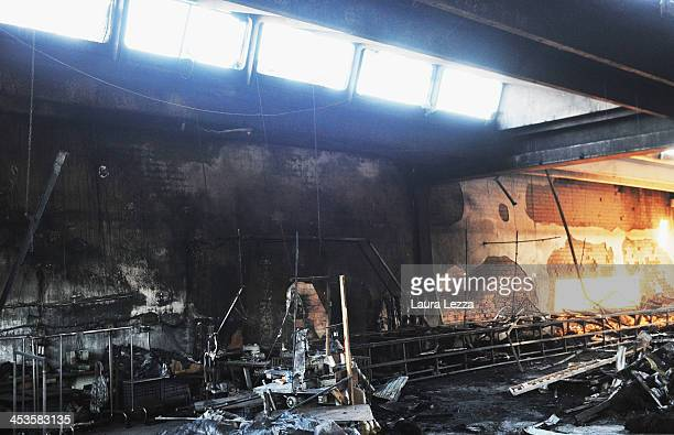 Debis sits inside a burned interior of a clothing factory after a fire where seven Chinese workers were burned to death on December 4 2013 in Prato...