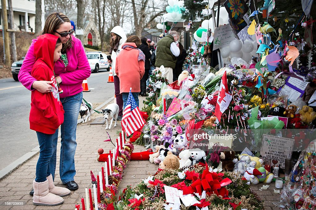 Deborah Gibelli holds her daughter, Alexandra Gibelli, age 9, while looking at a memorial for those killed in the school shooting at Sandy Hook Elementary School, on December 24, 2012 in Newtown, Connecticut. Donations and letters are pouring in from across the country as the town tries to recover from the massacre.