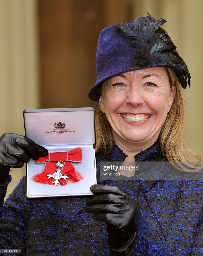 Deborah Hale proudly holds her Member of the British Empire (MBE) medal after it was presented to her by Queen Elizabeth II at the Investiture Ceremony at Buckingham Palace on February 13, 2012 in London, England.