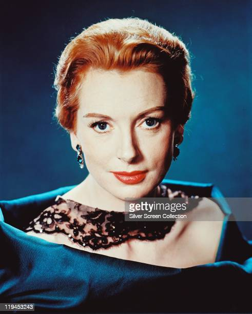 Deborah Kerr British actress wearing a black lace collar and a blue silk gown in a studio portrait against a blue background circa 1950