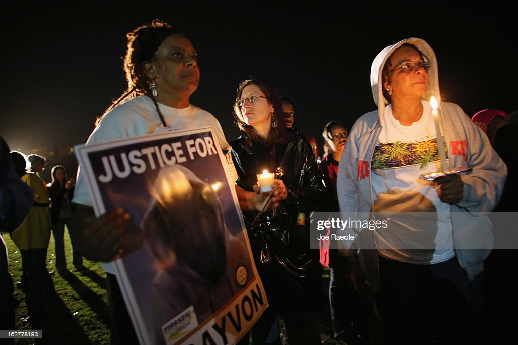 Debra (who didn't want to use her last name), Julie Lambakis and Jeanette Holloway gather with others for a candle light vigil at Fort Mellon Park to mark the one year anniversary of when Trayvon Martin was killed on February 26, 2013 in Sanford, Florida. Martin was shot by George Zimmerman on February 26, 2012 while Zimmerman was on neighborhood watch patrol in the gated community of The Retreat at Twin Lakes in Sanford, Florida.