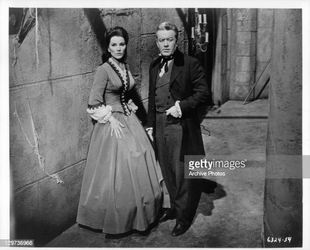 Debra Paget and Frank Maxwell standing in cobweb covered hallway in a scene from the film 'Haunted Palace' 1963