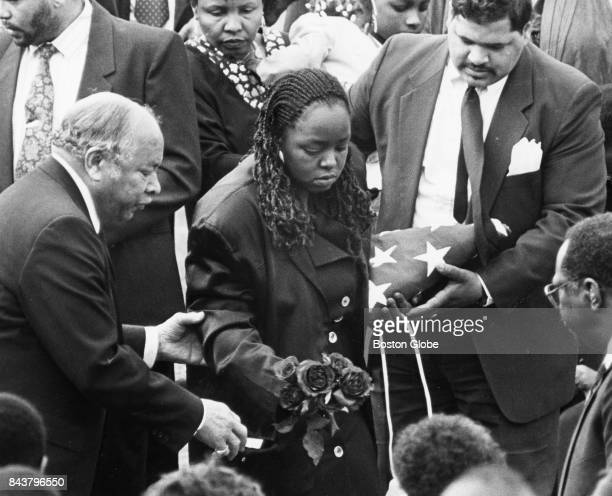 Debra Sarjeant the wife of murder victim Charleston Sarjeant places flowers on her husband's casket at Oak Lawn Cemetery in Boston on May 1 1992 Her...