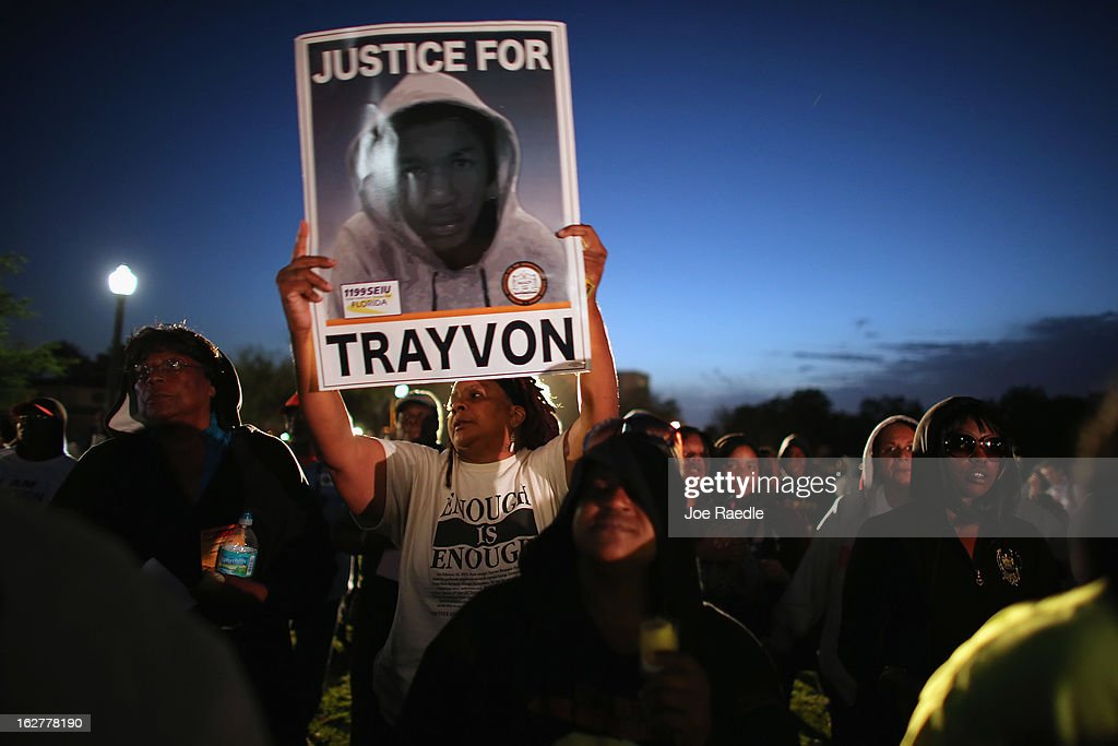 Debra (who didn't want to use her last name) stands with a sign as she and others hold a vigil at Fort Mellon Park to mark the one year anniversary of when Trayvon Martin was killed on February 26, 2013 in Sanford, Florida. Martin was shot by George Zimmerman on February 26, 2012 while Zimmerman was on neighborhood watch patrol in the gated community of The Retreat at Twin Lakes in Sanford, Florida.
