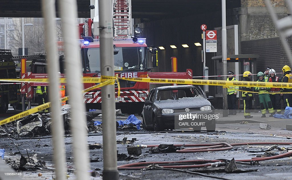 Debris and a burntout car are pictured at the scene of a helicopter crash in central London, on January 16, 2013. Two people were killed when a helicopter hit a crane at a building site in central London and plunged to the ground on Wednesday, police said. AFP PHOTO / CARL COURT