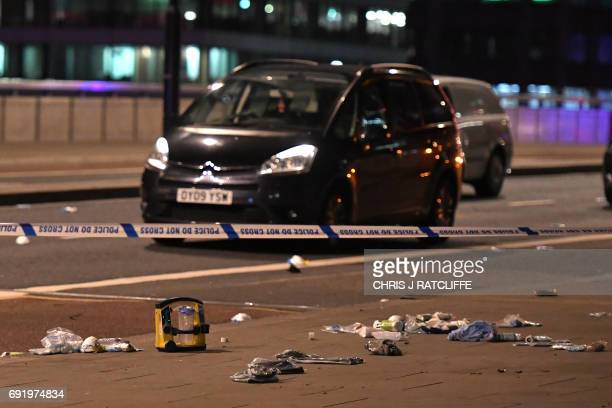 TOPSHOT Debris and abandoned cars remain on London Bridge at the scene of an apparent terror attack in central London on June 3 2017 Armed police...