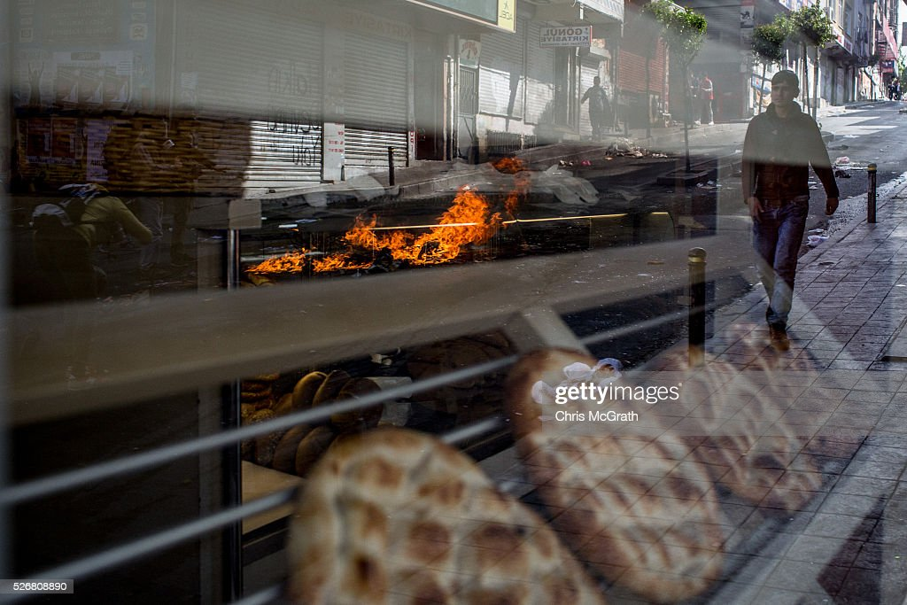 Debris burns on a street reflected in the window of a bakery after police dispersed protesters in the Okmeydani neighbourhood during a May Day demonstration on May 1, 2016 in Istanbul, Turkey. Turkish police used tear gas and water cannon to disperse protesters as they tried to make their way to Taksim Square.
