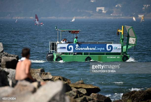 A debris collecting boat sails before the first day of Aquece Rio the International Sailing Regatta 2014 as the first test event for the Rio 2016...