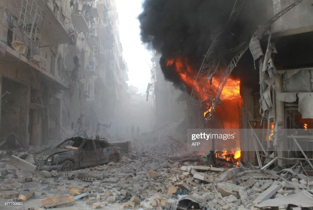 Debris cover a street and flames rise from a building following a reported air strike by Syrian government forces on March 7 2014 during the Friday...