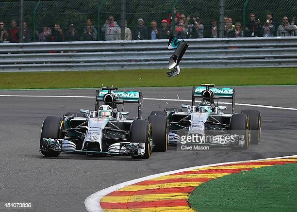 Debris flies in the air as Nico Rosberg of Germany and Mercedes GP makes contact with Lewis Hamilton of Great Britain and Mercedes GP during the...