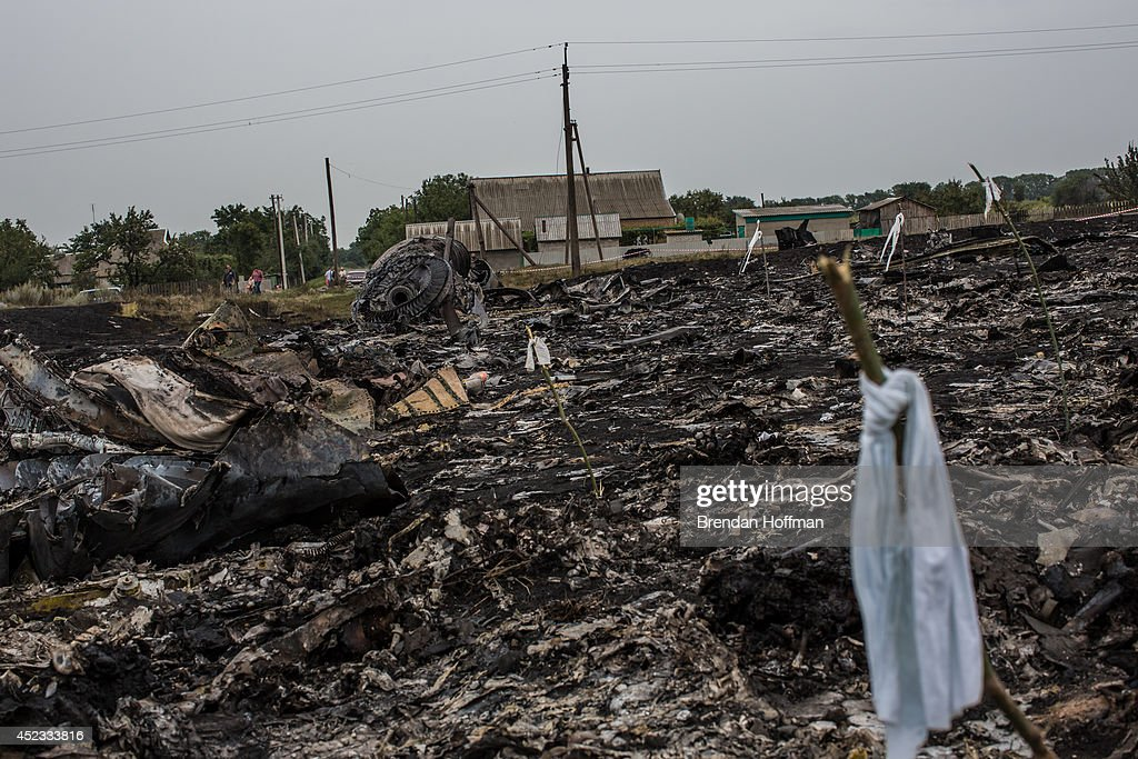 Debris from an Malaysia Airlines plane crash including a white ribbon tied to a stick which indicates the presence of human remains lies in a field...