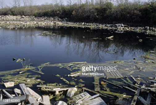 Debris from city landfill overflowing into water : Stock Photo