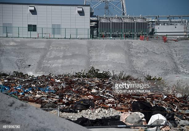 Debris from the 2011 tsunami sits piled up at the Fukushima Daiichi nuclear power plant in Okuma Fukushima prefecture on October 9 2015 Tokyo...