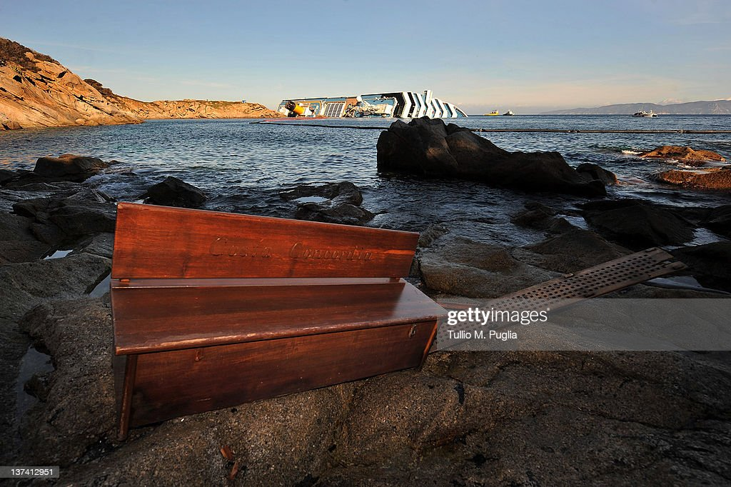 Debris from the cruise ship Costa Concordia is washed up as the vessel lies stricken in the background off the coast of the island of Giglio on January 20, 2012 in Giglio Porto, Italy. The rescue operation to find missing passengers aboard Costa Concordia was suspended again today, as the vessel shifted on the rocks on which it is resting.