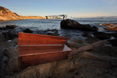 Debris from the cruise ship Costa Concordia is washed up as the vessel lies stricken in the background off the coast of the island of Giglio on...