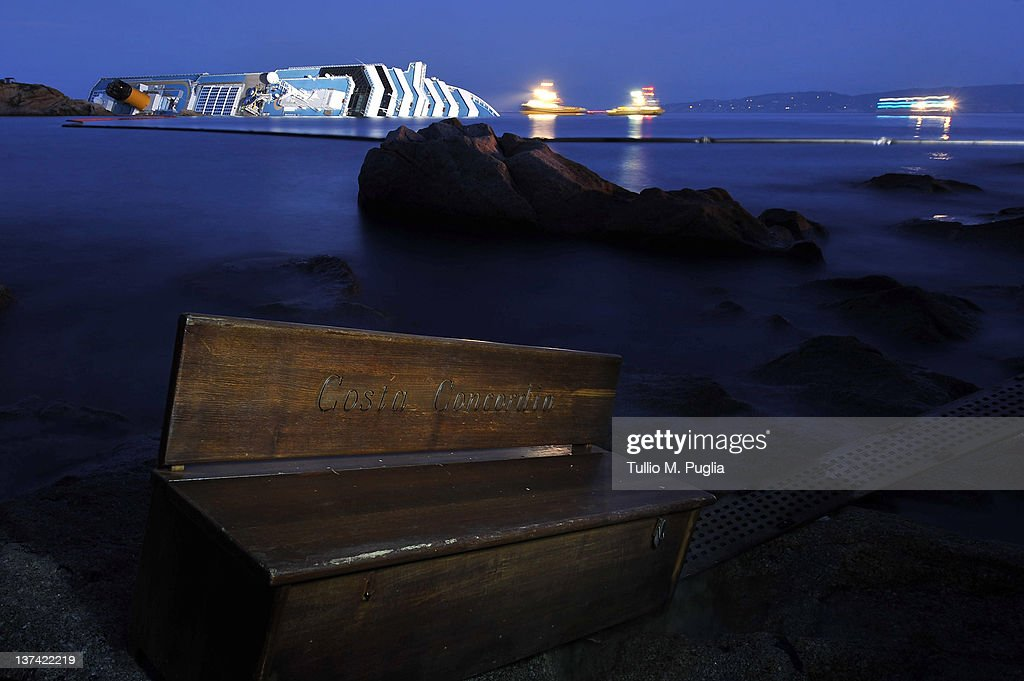Debris from the cruise ship Costa Concordia is washed up as the vessel lies stricken in the background off the coast of the island of Giglio on January 20, 2012 in Giglio Porto, Italy. The rescue operation to find 21 people still missing aboard the Costa Concordia resumed after being suspended again today, as conditions caused the vessel to shift on the rocks on which it is resting.