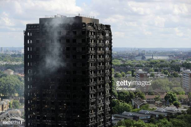 Debris hangs from the blackened exterior of Grenfell Tower on June 15 2017 in London England At least 17 people have been confirmed dead and dozens...