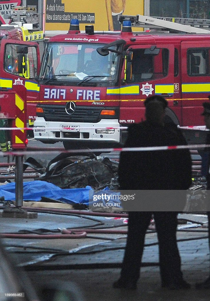 Debris is pictured in front of a fire engine at the scene of a helicopter crash in central London, on January 16, 2013. Two people were killed when a helicopter hit a crane at a building site in central London and plunged to the ground on Wednesday, police said.
