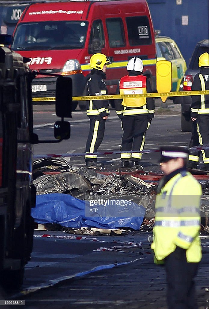 Debris is pictured in front of a fire engine at the scene of a helicopter crash in central London on January 16, 2013. Two people were killed when a helicopter hit a crane at a building site in central London during morning rush hour and plunged to the ground, engulfing several cars in flames.