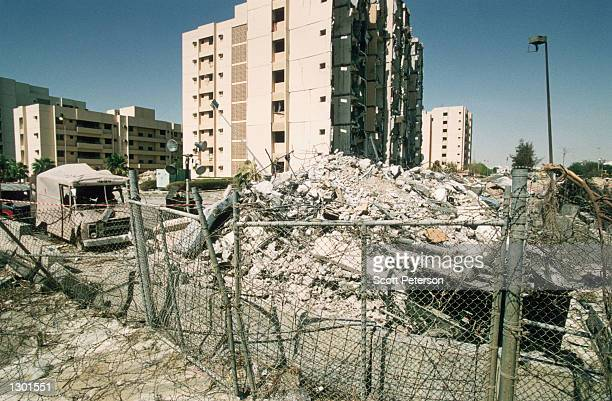 Debris is piled up near the wreckage of Khobar Towers in Dhahran Saudi Arabia June 29 1996 after a truck bomb exploded four days previously killing...