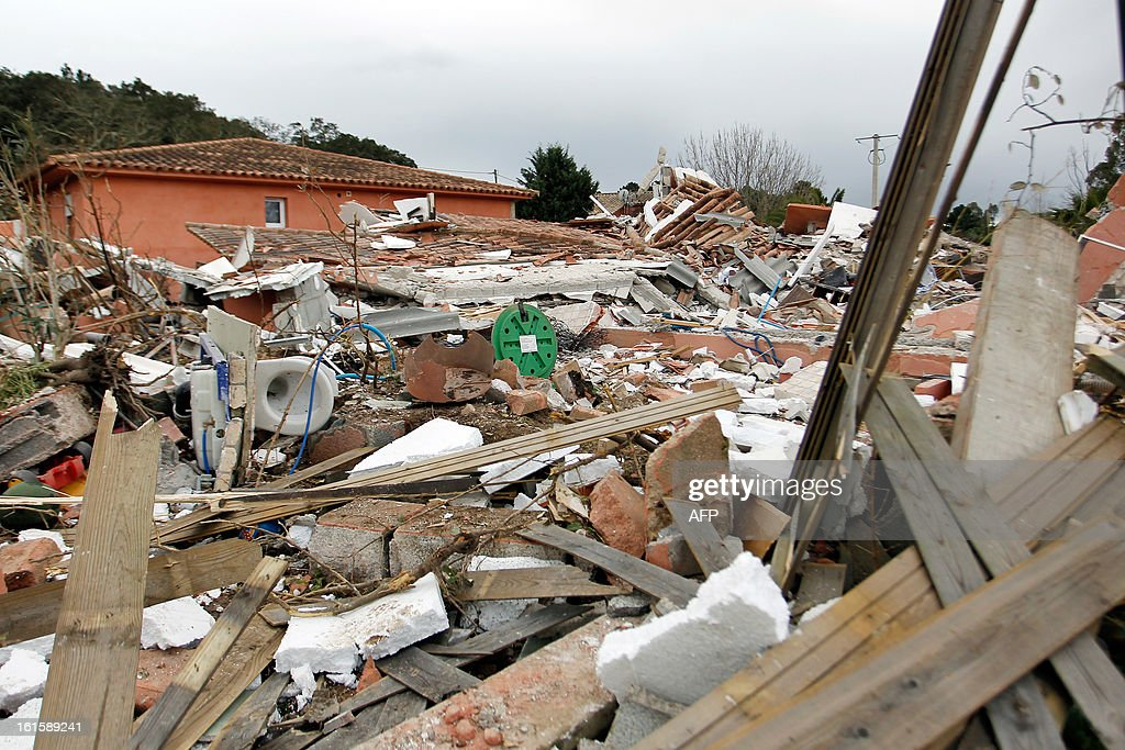 Debris lay on the ground of a house destroyed by a blast, injuring a man and a child, on February 12, 2013, in Porto-Vecchio, in the French Mediterranean island of Corsica. The reasons of the blast are still unknown.