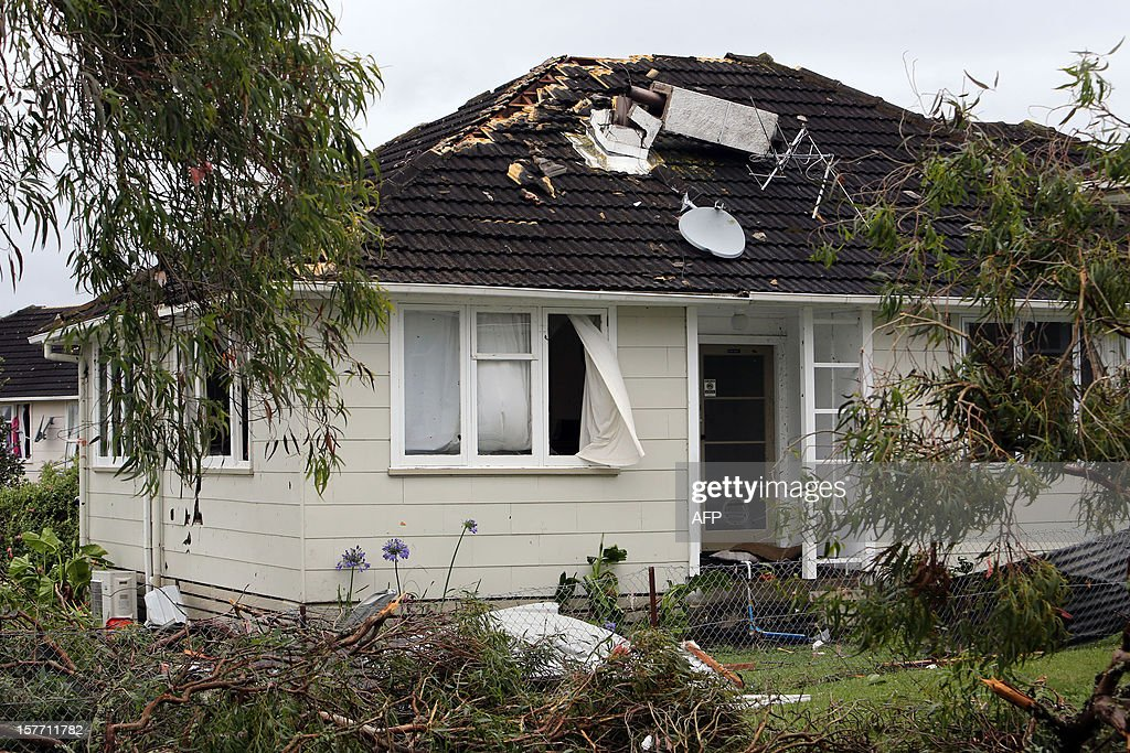 Debris lies in front of a damaged house in Hobsonville, Auckland on December 6, 2012 after packed wind gusts of up to 110 kilometres (70 miles) per hour, struck suburban Hobsonville in the afternoon. A freak storm described by police as a tornado hit New Zealand's largest city Auckland on December 6 causing 'utter devastation', with three people reportedly killed in ferocious winds. AFP PHOTO / Michael Bradley