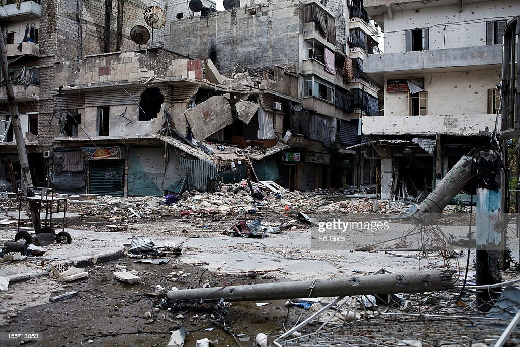 Debris litters the street in front of heavily damaged apartment buildings in the Salahudeen district on November 2, 2012 in Aleppo, Syria. The Shohada al Haq, or 'Martyrs of Truth' brigade control an area on the edge of the Salahudeen district in Aleppo, Syria's largest city. The brigade is made up of around 70 men, holding a handful of positions hidden in apartment blocks on the front line of Aleppo, facing toward Syrian army positions sometimes less than one hundred meters away. The Shohada al Haq use snipers to target Syrian regime troops as they move on the other side of the front, as well as moving between apartment blocks in the 'no man's land' between the two forces, occupying positions of advantage over the Syrian military. The brigade, or 'Katiba', live in the apartments they occupy, and the unit of rebel fighters is made up of former soldiers who defected from the Syrian military alongside men from Aleppo and other cities across Syria who have chosen to fight in Syria's increasingly violent civil war. (Photo by Ed Giles/Getty Images).