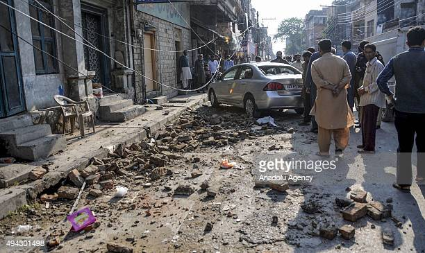 Debris of buildings and panicked Pakistani residents are seen in the streets following a massive earthquake in Rawalpindi Pakistan on October 26 2015...