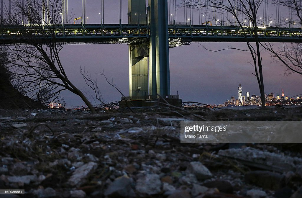 Debris sits on a still-closed beach area damaged by flooding from Hurricane Sandy near the Verrazano-Narrows Bridge with Lower Manhattan at back right on March 1, 2013 in the Staten Island borough of New York City. A government plan to purchase properties in Staten Island damaged by the storm remains on track.