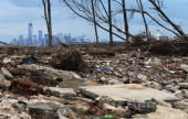 Debris sits on a stillclosed beach area damaged by flooding from Hurricane Sandy with Lower Manhattan at back left on March 1 2013 in the Staten...