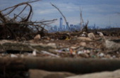 Debris sits on a stillclosed beach area damaged by flooding from Hurricane Sandy with Lower Manhattan and One World Trade Center in the background on...