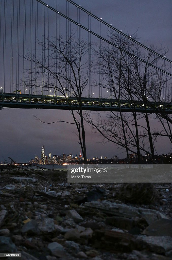 Debris sits on a still-closed beach area damaged by flooding from Hurricane Sandy near the Verrazano-Narrows Bridge in Staten Island with Lower Manhattan at back left on March 1, 2013 in the Staten Island borough of New York City. A government plan to purchase properties in Staten Island damaged by the storm remains on track.
