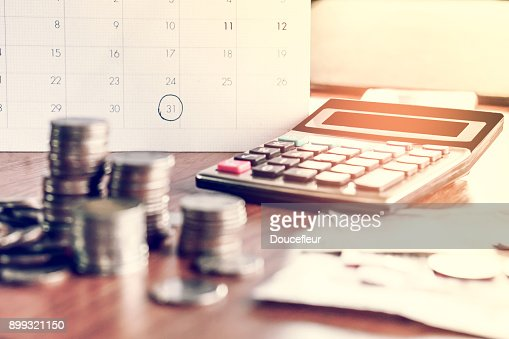 debt collection and tax season concept with deadline calendar remind note,coins,banks,calculator on table : Stock Photo