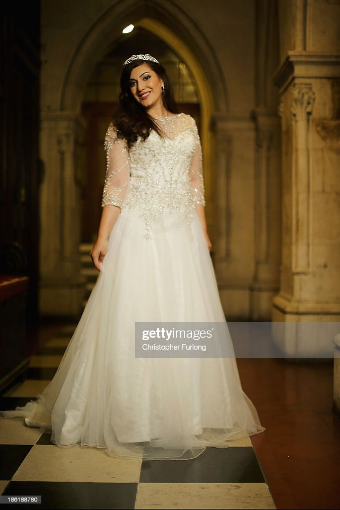 Debutante Eeman Alansari, aged 20, from Dubai, poses as she awaits the arrival of guests during the Queen Charlotte's Ball at the Royal Courts of Justice on October 26, 2013 in London, England. Queen Charlotte's Ball is the pinnacle event in the London Season. The London Season is rich in history and was formed over two hundred years ago when the custom of returning to London at the end of the hunting season was celebrated with glittering balls and high society events. The modern group of meticulously selected debutantes continue the tradition and celebrate their year of charity fund raising, etiquette classes and debut at The Queen Charlotte's Ball. The young ladies, usually aged between 17 and 20 and wearing designer dresses, attend the grand ball where they are presented to guests and curtsey to the Queen Charlotte Cake. King George III introduced the Queen Charlotte's Ball in 1780 to celebrate his wife's birthday and debutantes were traditionally presented to the King or Queen until 1958.