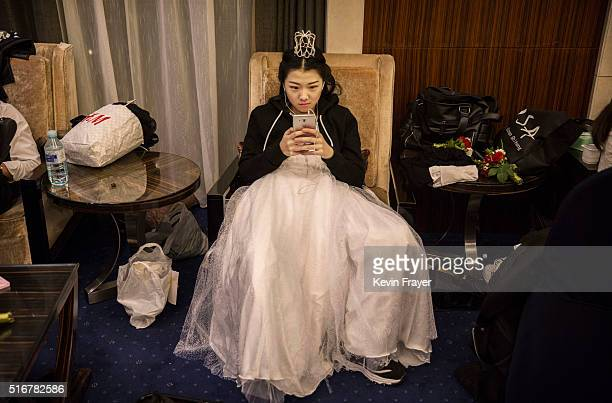 A debutante from a local academy looks at her mobile phone as she waits to take part in the Vienna Ball at the Kempinski Hotel on March 19 2016 in...