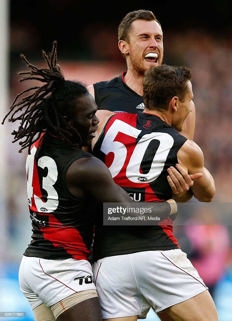 Debutante, James Polkinghorne of the Bombers celebrates a goal with Anthony McDonald-Tipungwuti (left) and Matthew Leuenberger (top) of the Bombers during the 2016 AFL Round 06 match between the Carlton Blues and the Essendon Bombers at the Melbourne Cricket Ground, Melbourne on May 1, 2016.