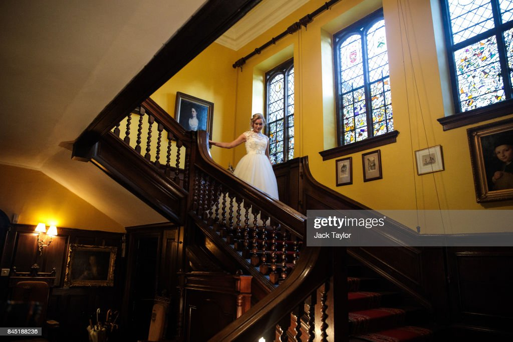 Debutante Olivia Mott, 20 from Charlottesville, Virginia, makes her way down the stairs at Boughton Monchelsea Place ahead of the Queen Charlotte's Ball on September 9, 2017 in Maidstone, England. In 1780 the first debutante's Ball was held by King George III to celebrate the birthday of his wife Queen Charlotte and raised money for a maternity hospital. Society girls were presented to the monarch and it became an annual event and important as a marriage market for the upper echelons of society. The London Season runs for six months of the year including sporting events, cocktail parties, dances and concerts and the Ball is the pinnacle of this season. After the present Queen terminated the practice of introducing debutantes at royal garden parties in 1957, Lady Howard de Walden followed by then editor of Tatler, Peter Townend, continued the tradition and on his death Peter nominated former debutantes Jennie Hallam-Peel and Patricia Woodall to take over running of The London Season. It is now focussed on raising money for children in need worldwide and the Queen Charlotte's Ball has been held in Shanghai and Dubai as well as various grand venues in London. This year the debutantes' gowns have been supplied by Berketex Brides and the cake, to which the debutantes curtsey, is made by Pretty Gorgeous Cakes.