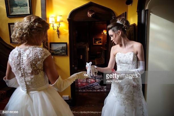 Debutante Olivia Mott from Charlottesville Virginia passes Callan Foran from Ohio a pair of white gloves as they prepare at Boughton Monchelsea Place...