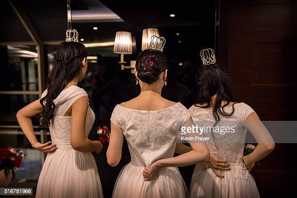 Debutantes from a local academy arrange their outfits before taking part in the Vienna Ball at the Kempinski Hotel on March 19 2016 in Beijing China...