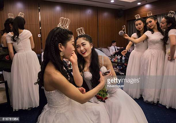 Debutantes from a local academy laugh as they get ready to take part in the Vienna Ball at the Kempinski Hotel on March 19 2016 in Beijing China The...