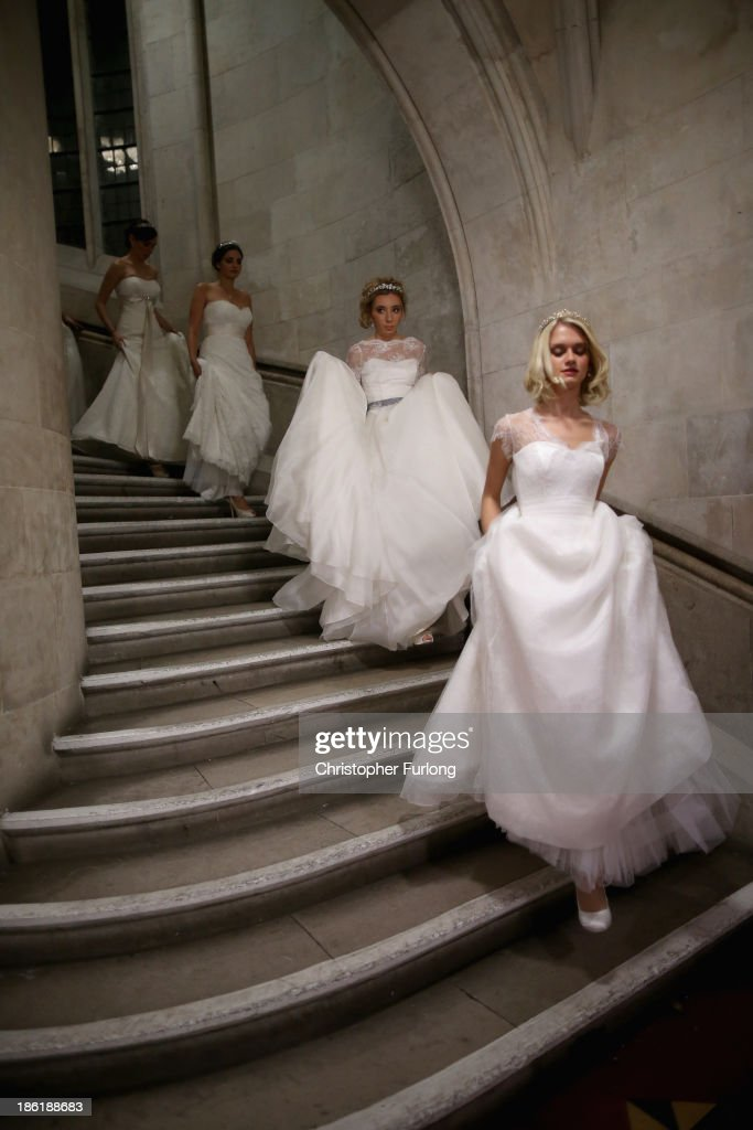 Debutantes make their way to the main hall during the Queen Charlotte's Ball at the Royal Courts of Justice on October 26, 2013 in London, England. Queen Charlotte's Ball is the pinnacle event in the London Season. The London Season is rich in history and was formed over two hundred years ago when the custom of returning to London at the end of the hunting season was celebrated with glittering balls and high society events. The modern group of meticulously selected debutantes continue the tradition and celebrate their year of charity fund raising, etiquette classes and debut at The Queen Charlotte's Ball. The young ladies, usually aged between 17 and 20 and wearing designer dresses, attend the grand ball where they are presented to guests and curtsey to the Queen Charlotte Cake. King George III introduced the Queen Charlotte's Ball in 1780 to celebrate his wife's birthday and debutantes were traditionally presented to the King or Queen until 1958.